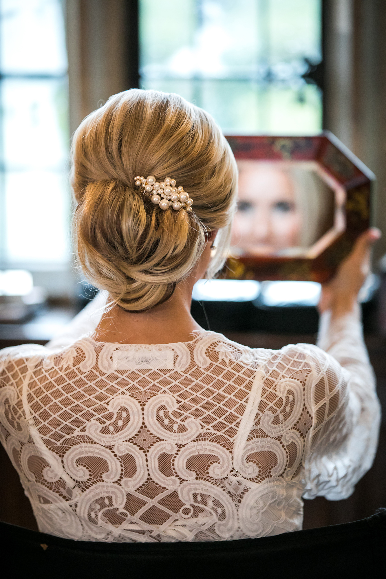 Bride looking at herself in a mirror, putting on makeup at Hengrave Hall before her Wedding