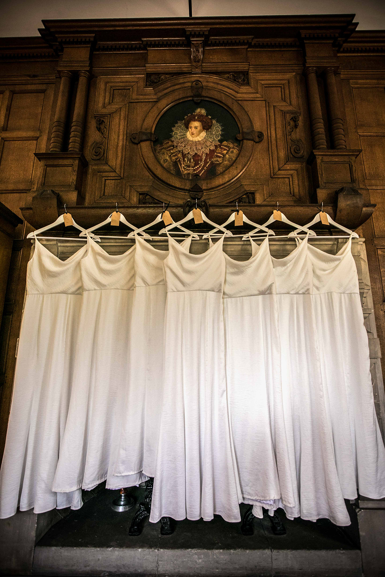 The Bridesmaids dresses hanging up in a stately Tudor room at Hengrave Hall