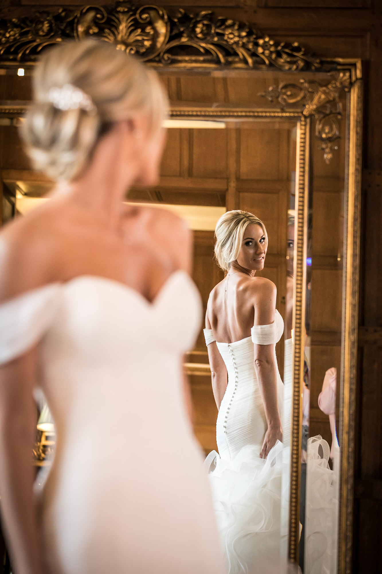 Bride looking at herself in a huge mirror, in a Stately Bedroom, at Hengrave Hall before her Wedding