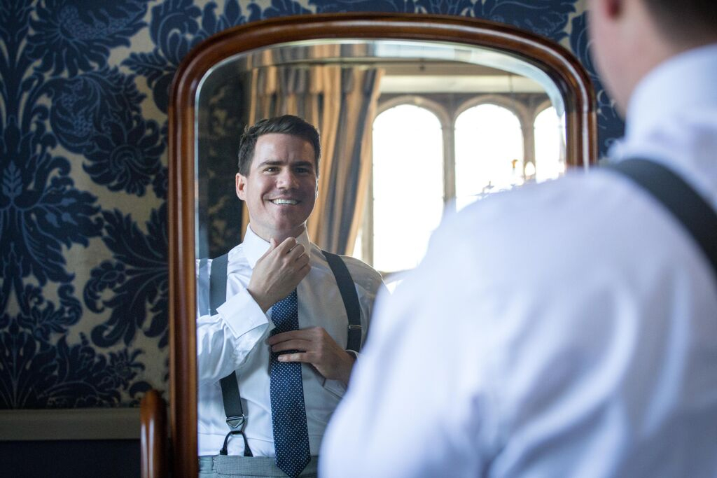 The groom smiling in a mirror and putting his tie on at Hengrave Hall