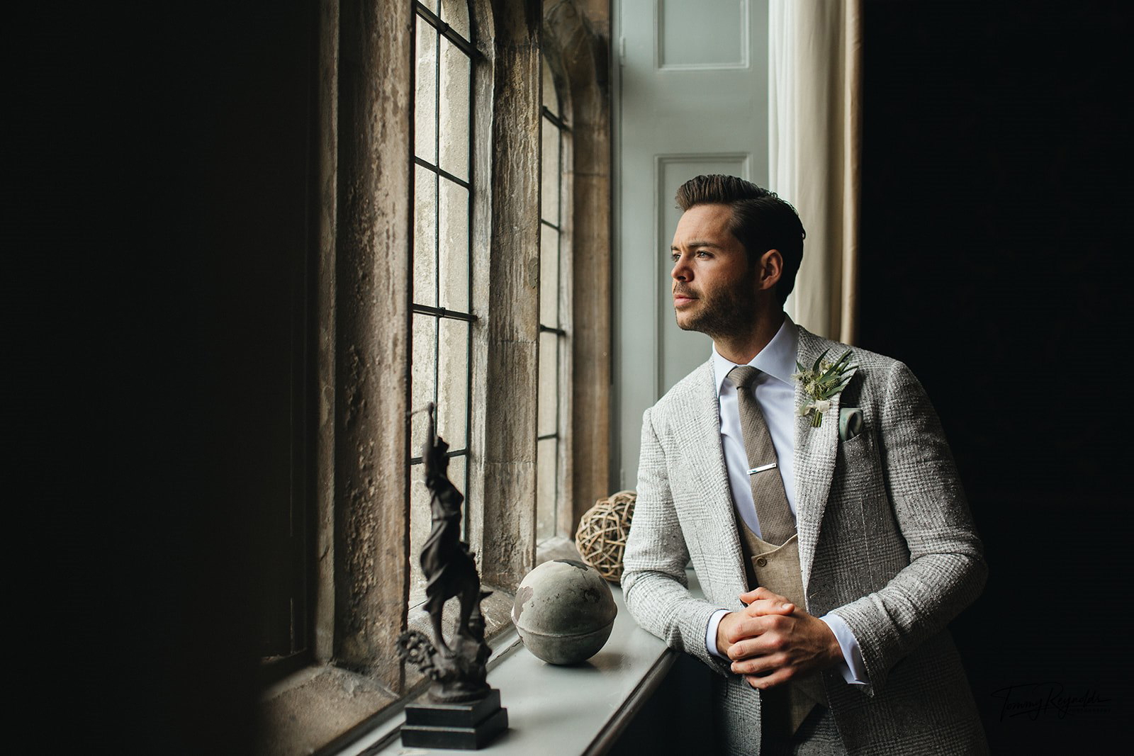 The groom reflecting and looking out of the window at Hengrave Hall