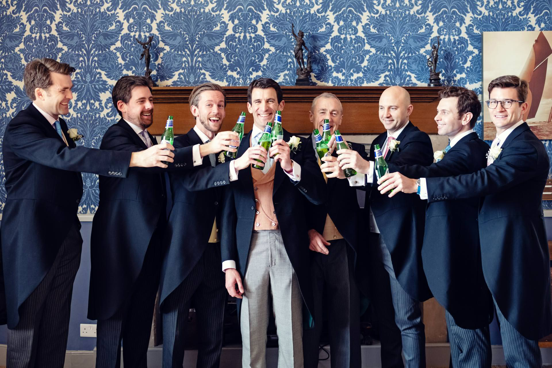 The groom, best man and ushers celebrating with beers before the wedding at Hengrave Hall