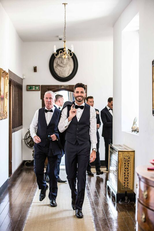 The groom, grooms father, best man and Ushers walking down the hallway at Hengrave Hall