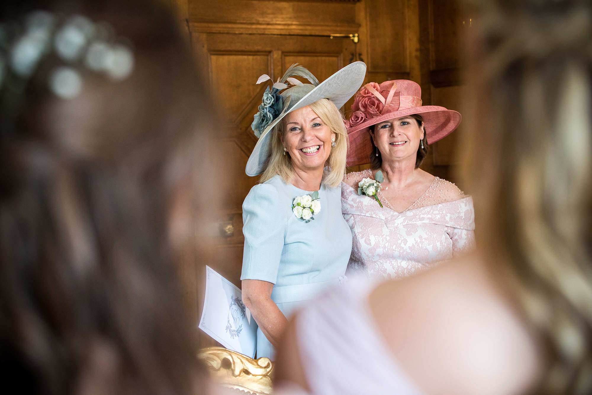 Two members of the wedding congregation smiling at the camera at Hengrave Hall