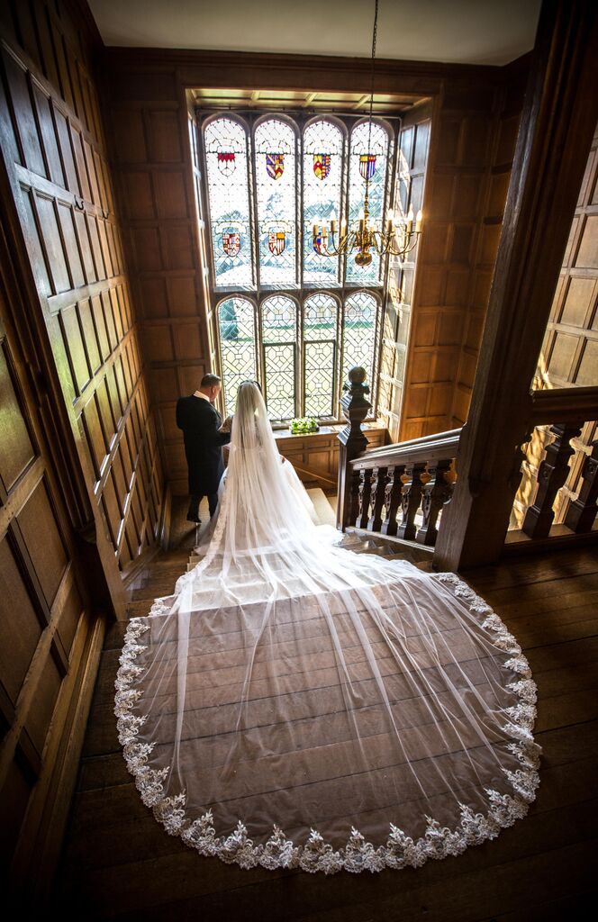 The Bride and father of the bride walking down the Tudor stairs in Hengrave Hall