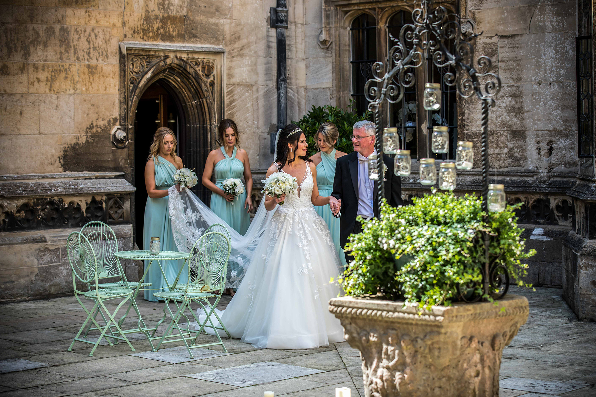 The bride, brides father and bridesmaids in the courtyard of Hengrave Hall