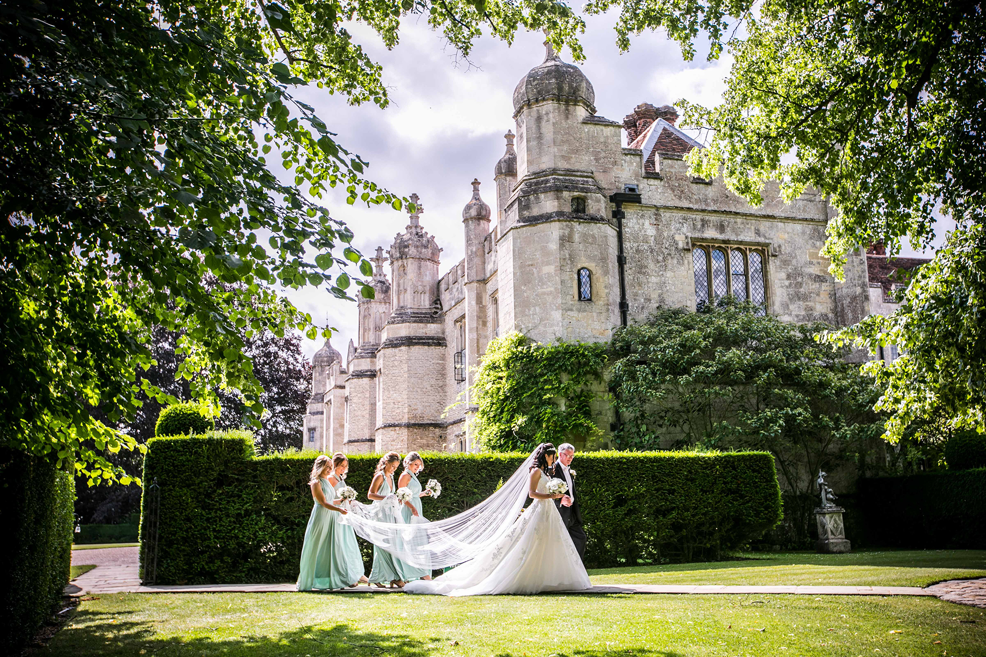 The bride, brides father and bridesmaids in the gardens of Hengrave Hall