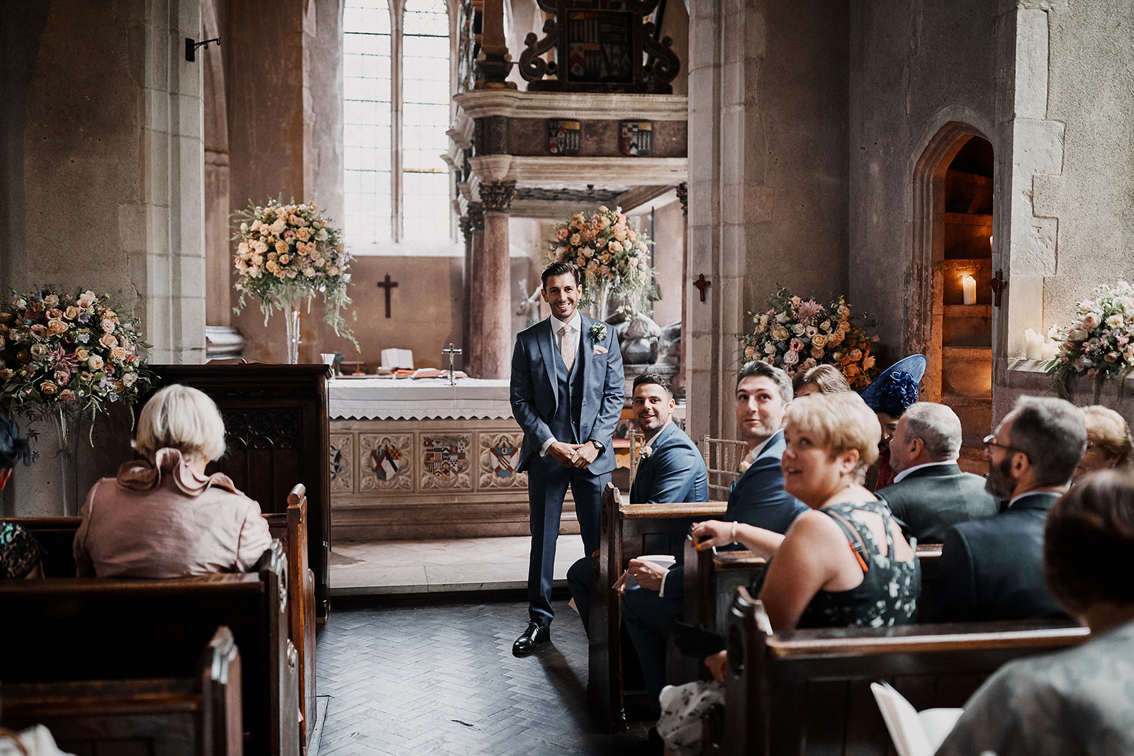 Groom and congregation waiting for the arrival of the bride, in the Church of St John Lateran, on the grounds of Hengrave Hall