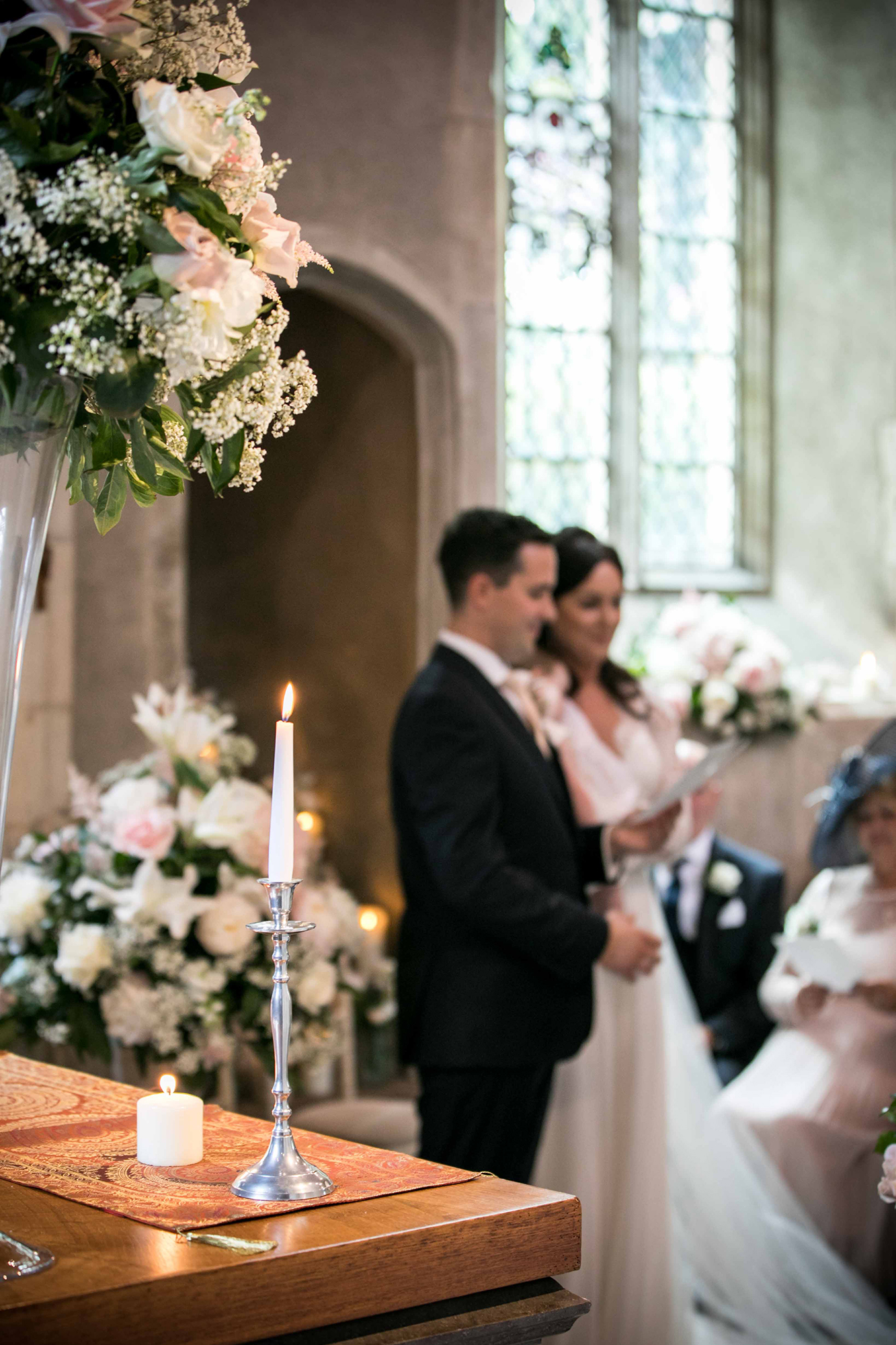 Couple taking their wedding vows at the Church of St John Lateran, on the grounds of Hengrave Hall