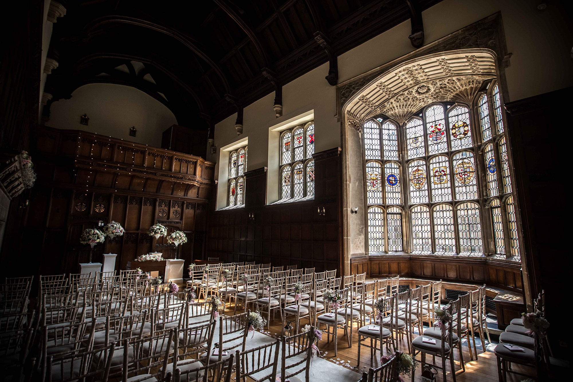 Interior of the Tudor hall, with beautiful imposing, stained glass windows, prepared for the wedding service at Hengrave Hall