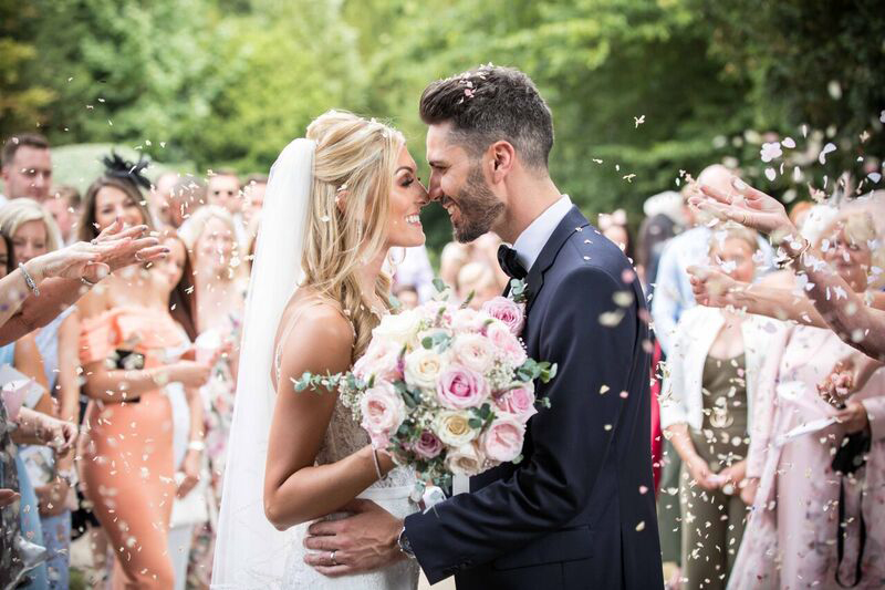 Newly married couple embracing and smiling, whilst being showered in confetti at Hengrave Hall