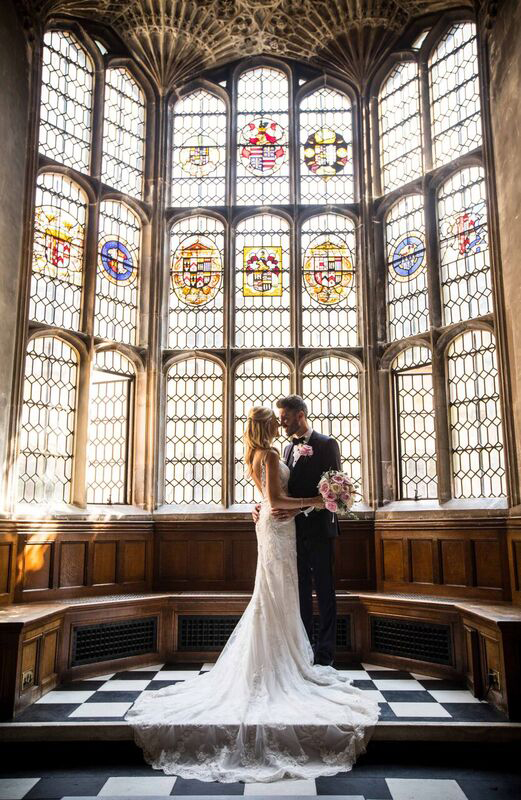Newly married couple in front of one of the large, intricate, Tudor windows at Hengrave Hall