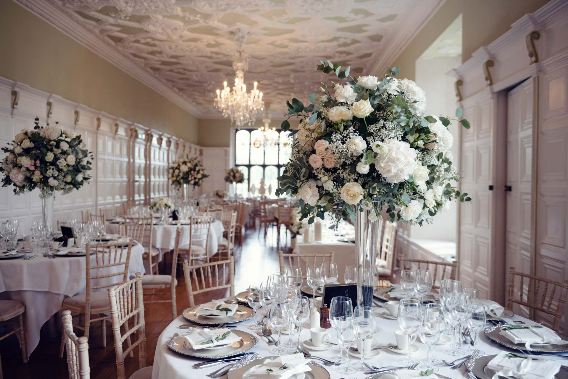 Beautifully laid tables in the banqueting Hall, with gorgeous flowers ready for a Wedding Breakfast at Hengrave Hall