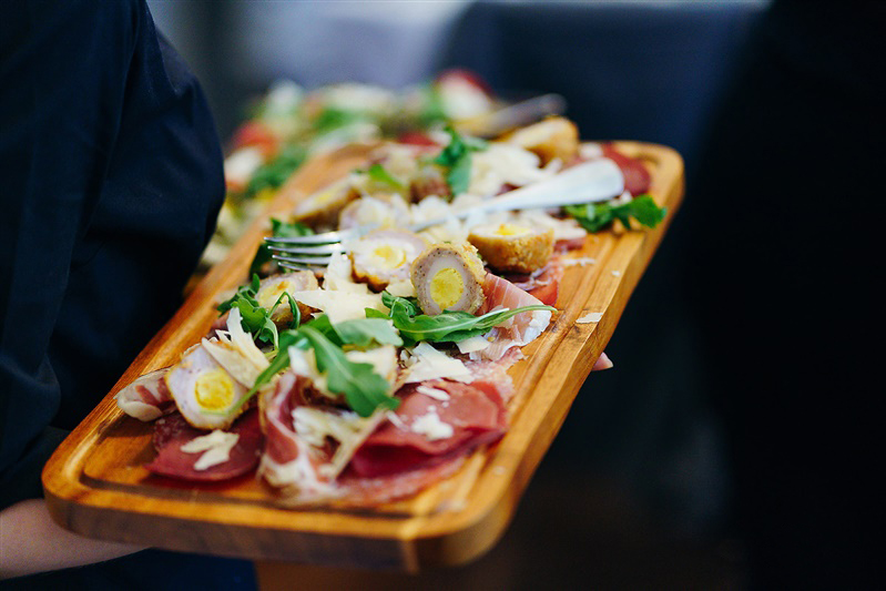 Close up of a gorgeous meat platter, on a rustic wooden board, served at Hengrave Hall
