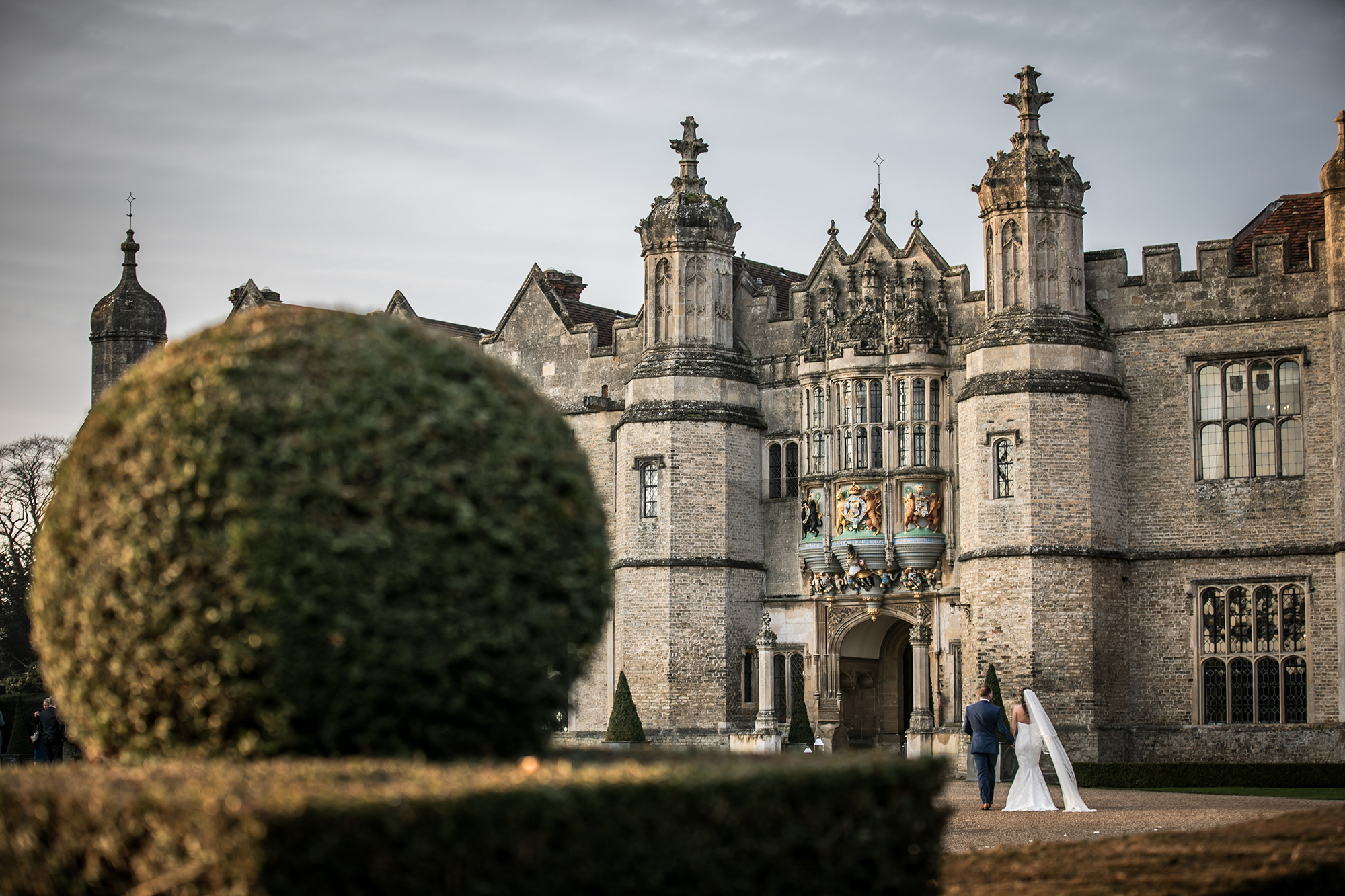 Newly married couple in the distance outside Hengrave Hall Wedding Venue