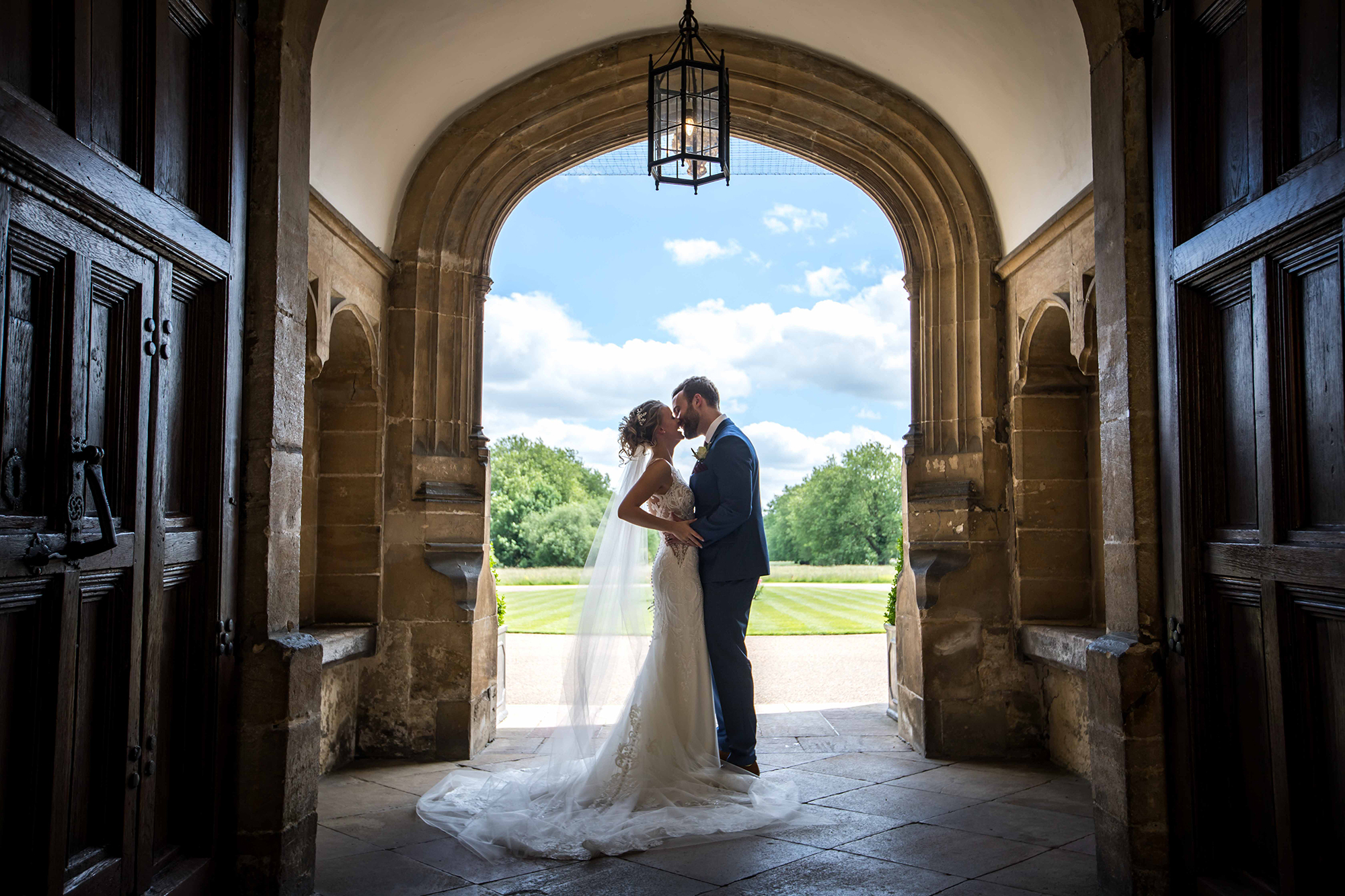 Newly married couple kissing in the entrance to Hengrave Hall