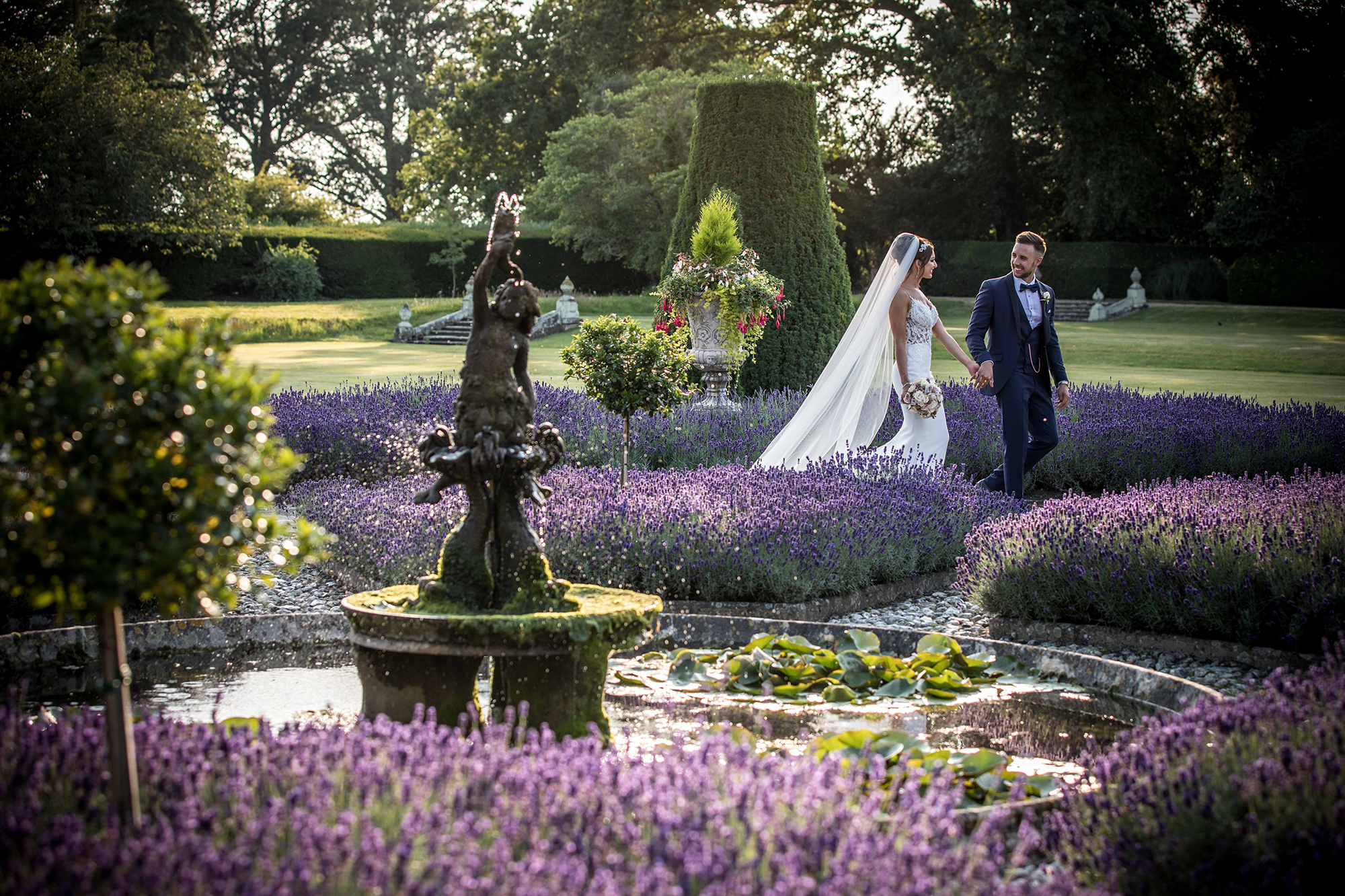 Newly married couple holding hands, walking through the lavender gardens at Hengrave Hall