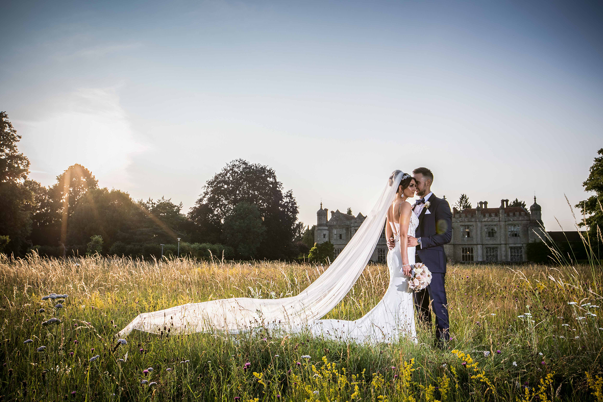 Newly married couple embrace in the meadow gardens at Hengrave Hall