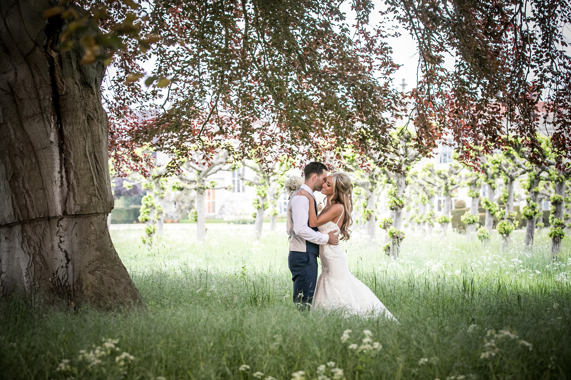 Newly married couple embrace under a tree in the gardens at Hengrave Hall