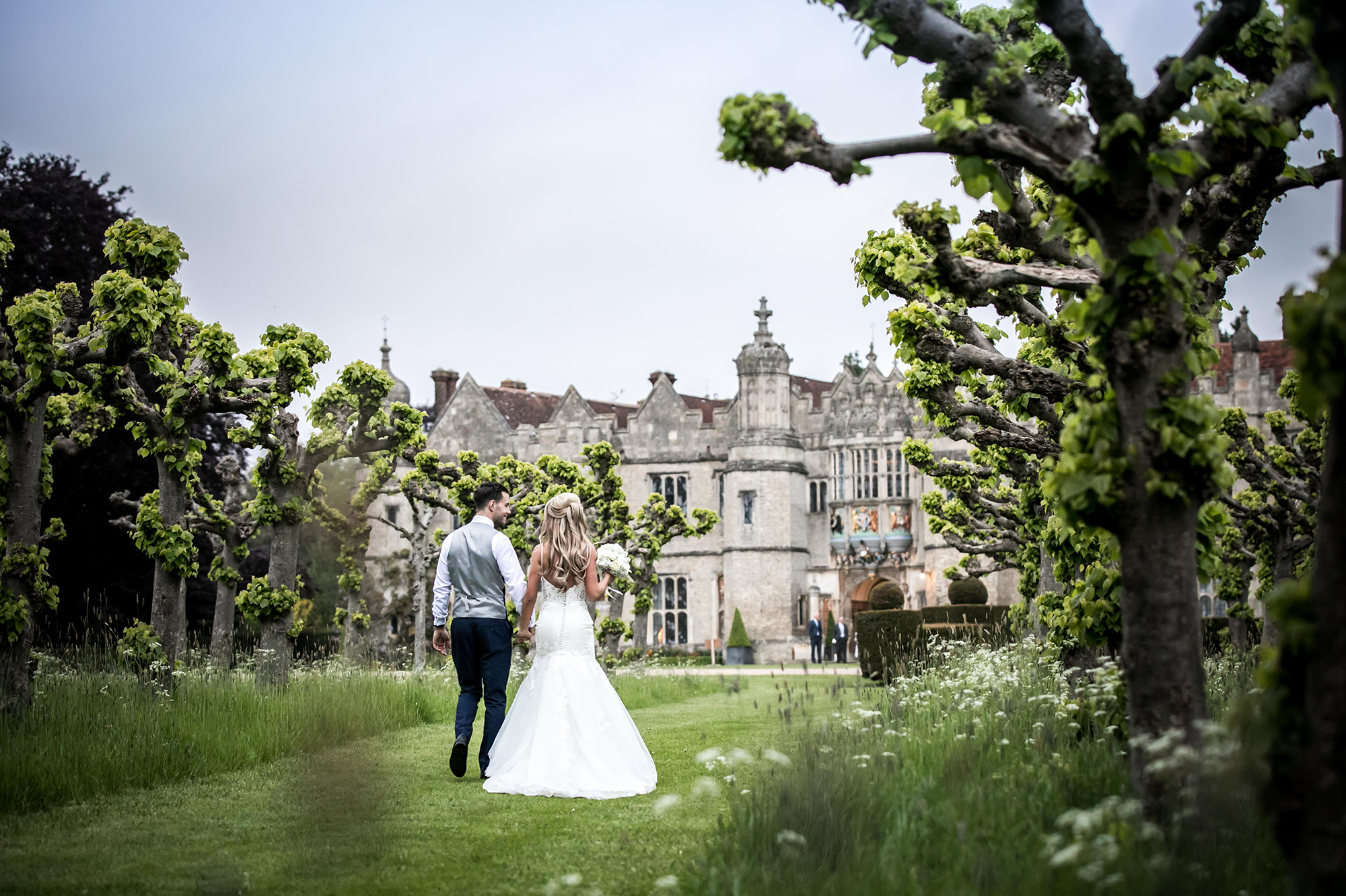 Newly married couple walking through the gardens towards Hengrave Hall