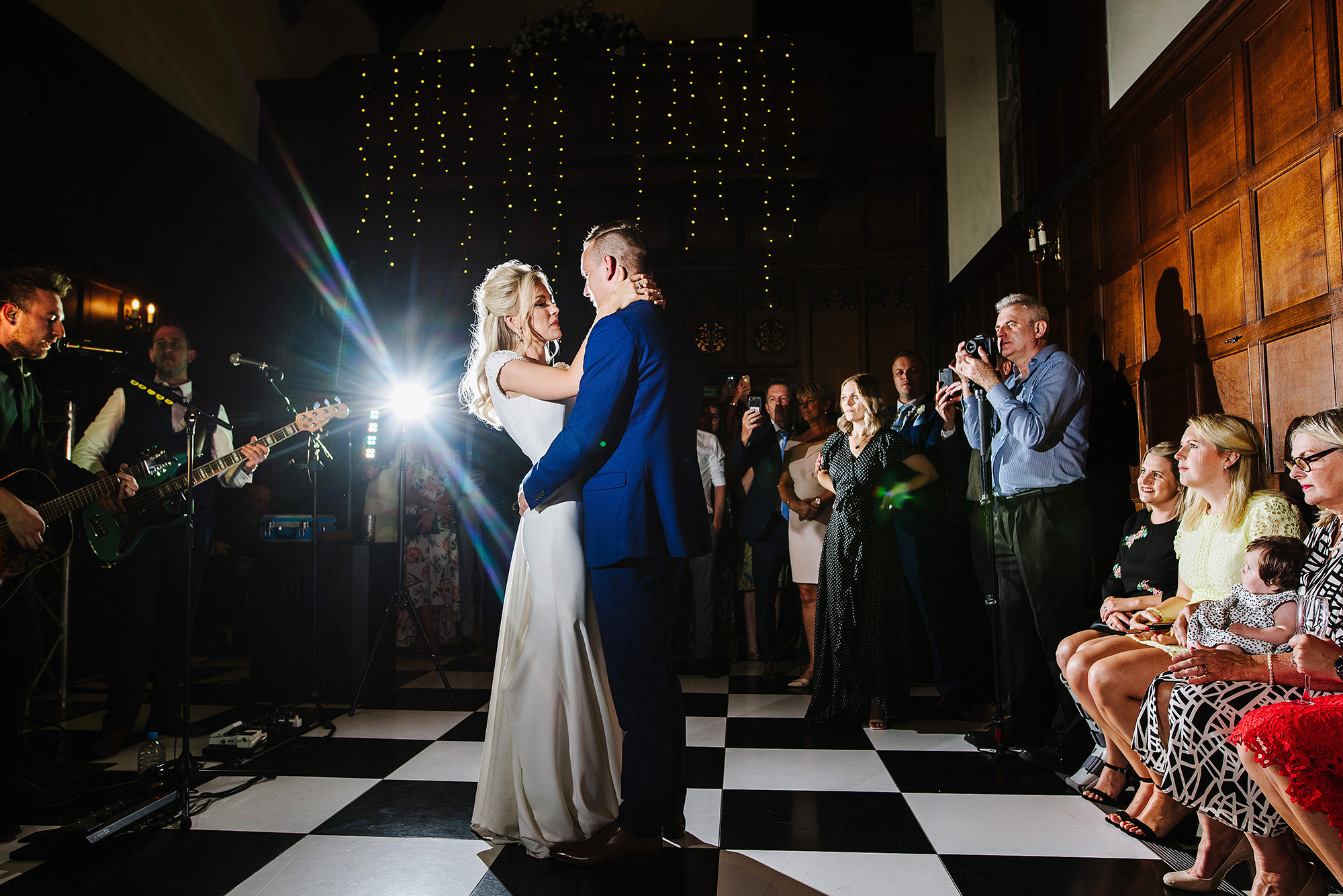 Newly married couple have their first dance played by a band at Hengrave Hall