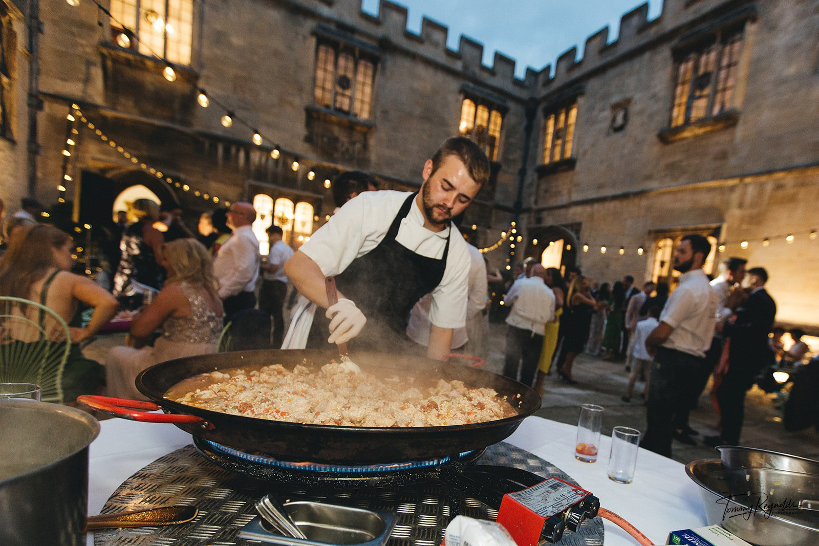 Evening reception paella being cooked in the courtyard at Hengrave Hall