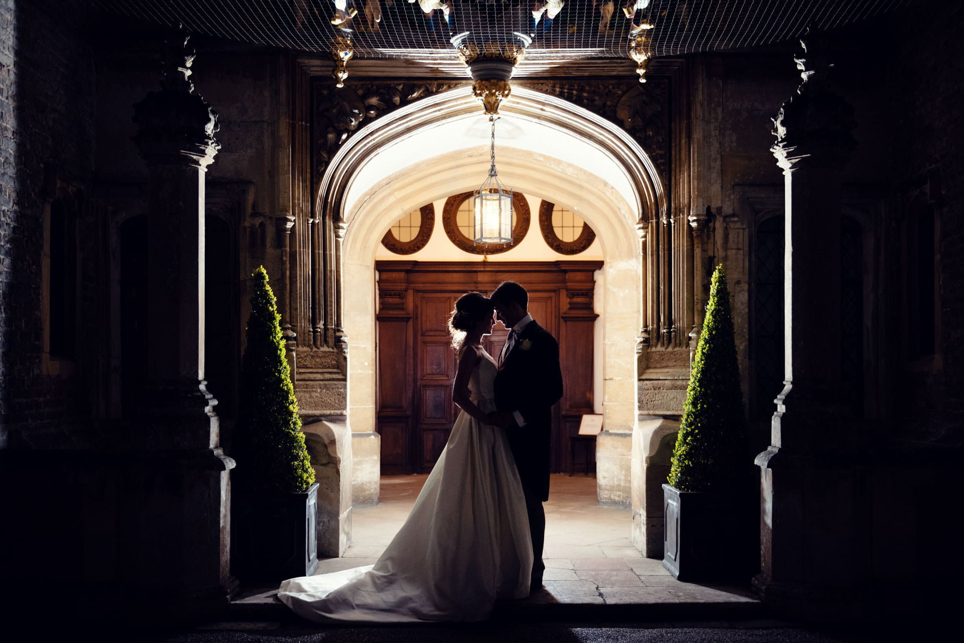 A silhouette of a newly married couple embrace in the hallway at Hengrave Hall