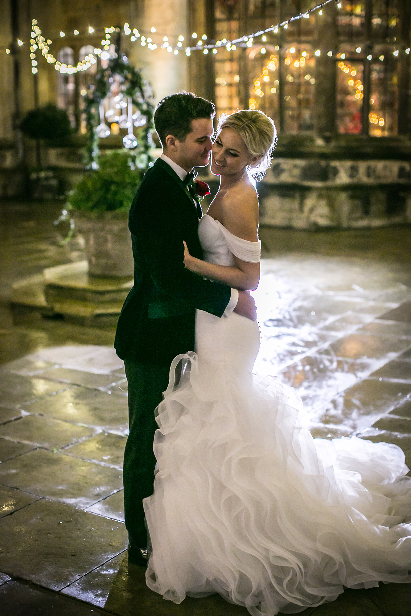 Newly married couple hug in the courtyard at Hengrave Hall