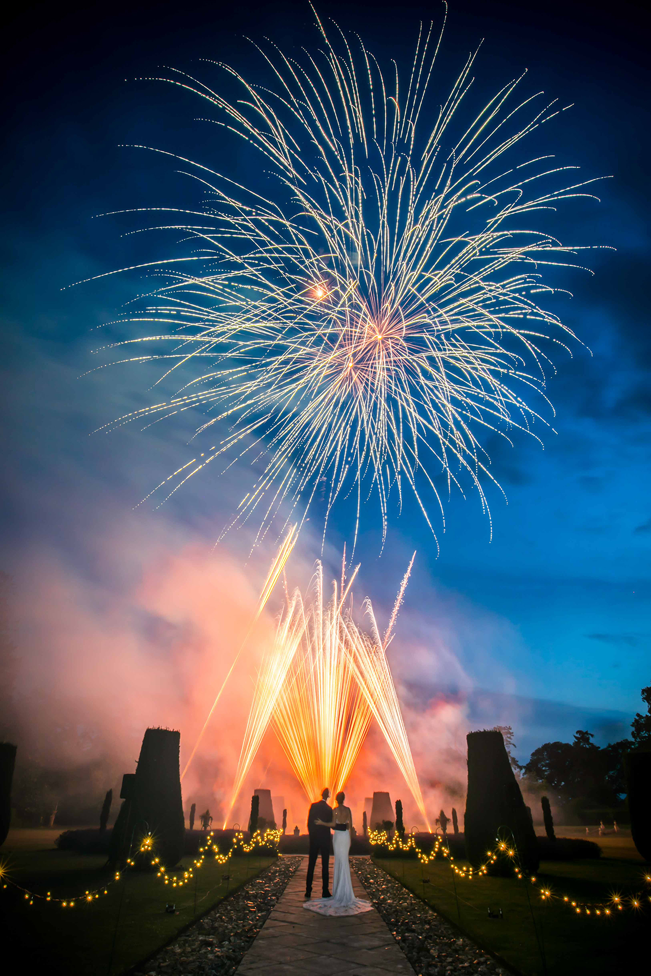 Newly married couple watch fireworks in the grounds of Hengrave Hall