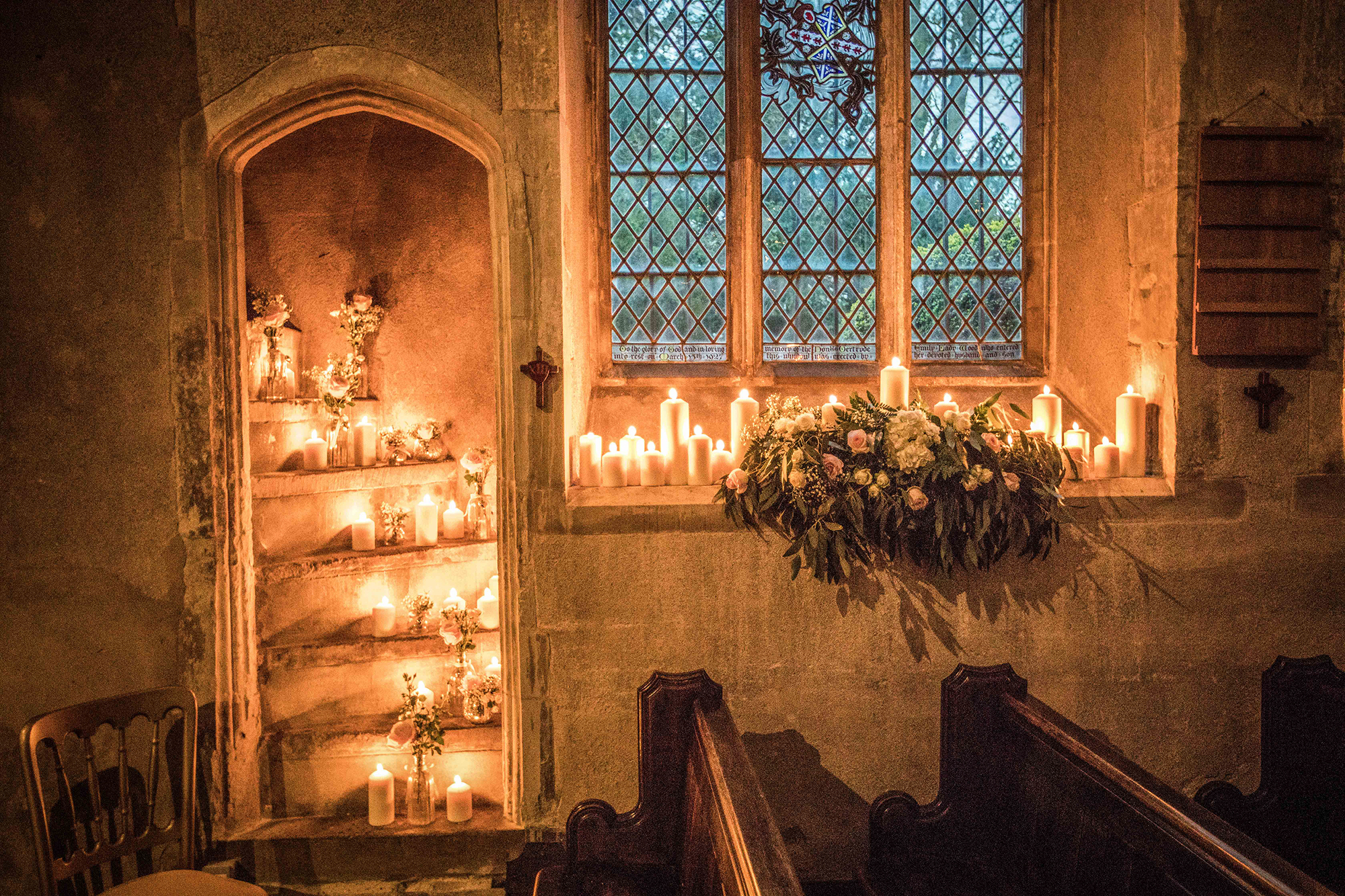 Lit candles and flowers in The Church of St John Latera at Hengrave Hall