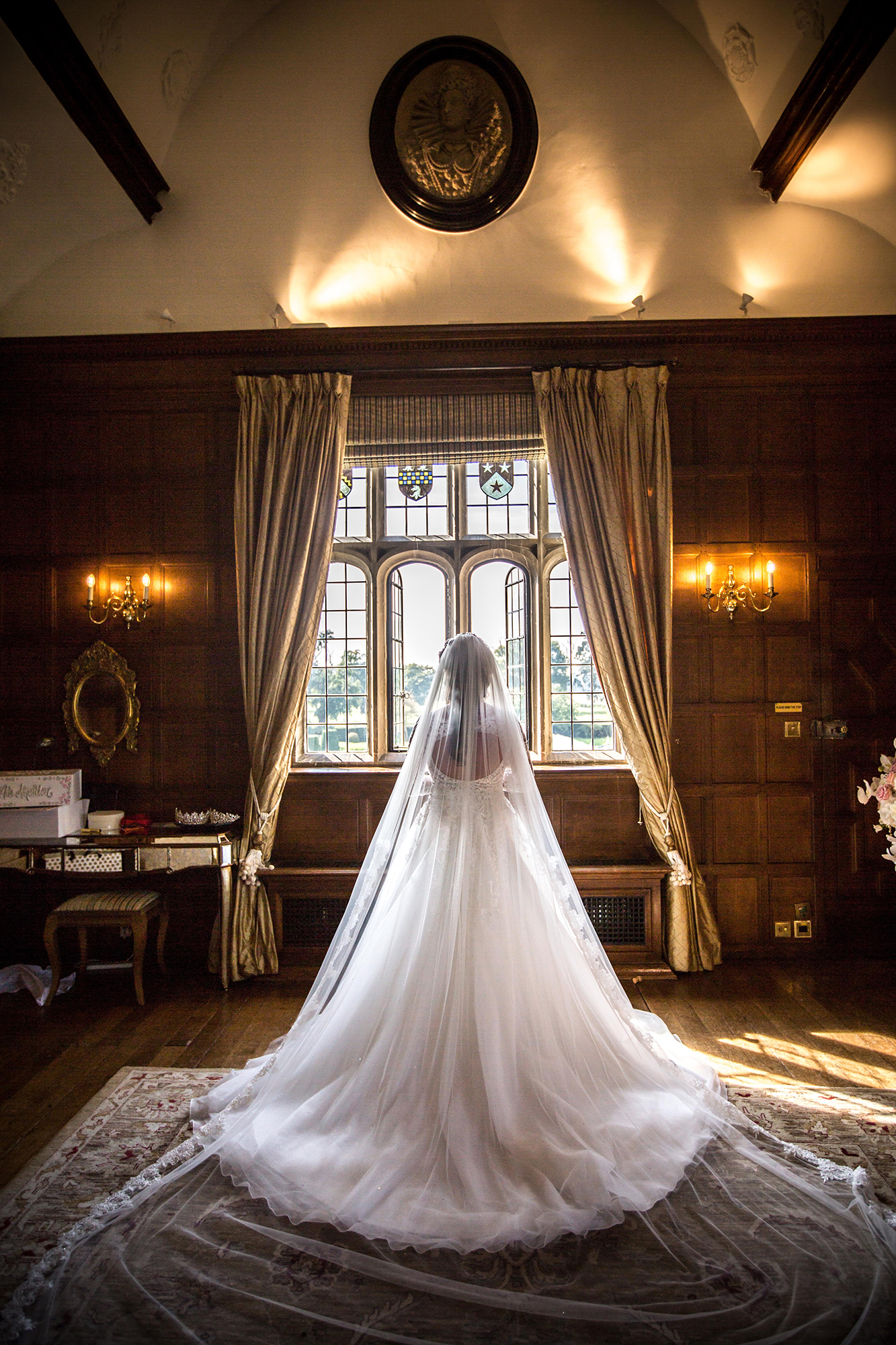 Bride in Wedding Dress looking over the grounds at Hengrave Hall