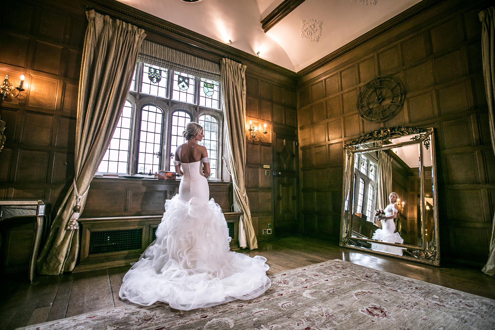 Bride looking at herself in a mirror, in a Stately Bedroom, at Hengrave Hall before her Wedding