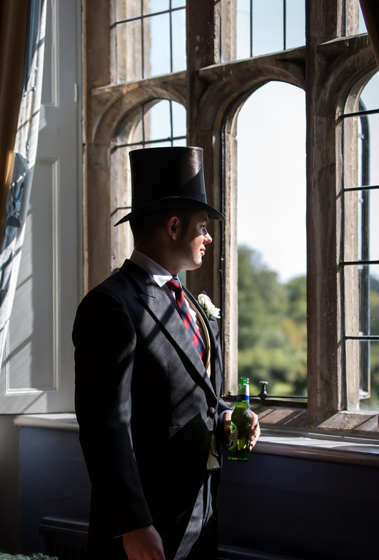 Man in top hat and tails, viewing the grounds at Hengrave hall