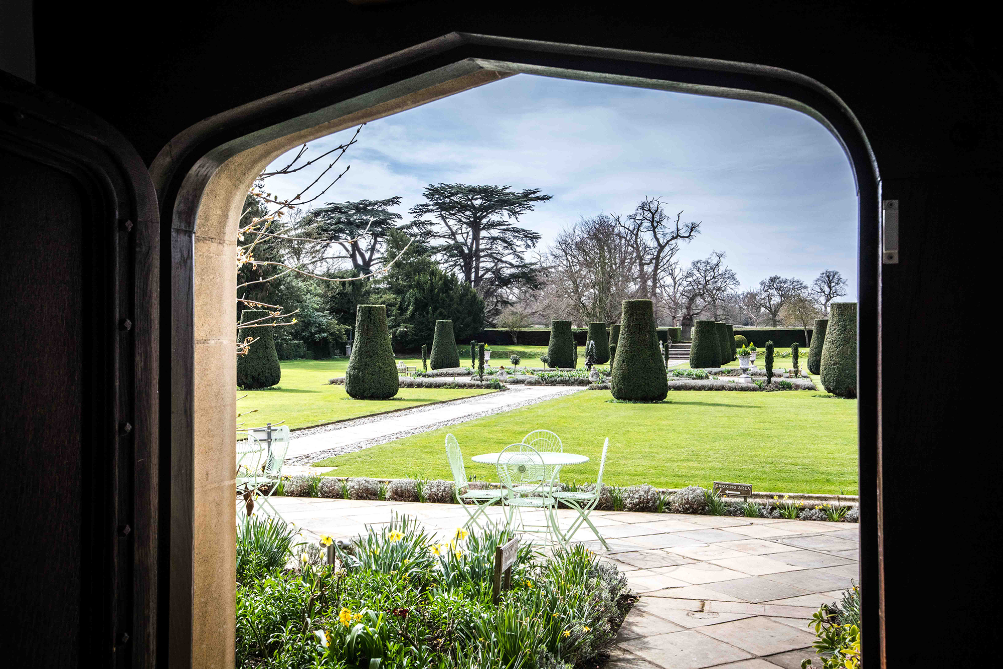 Grounds at Hengrave Hall Wedding Venue, through a Tudor door in early Spring