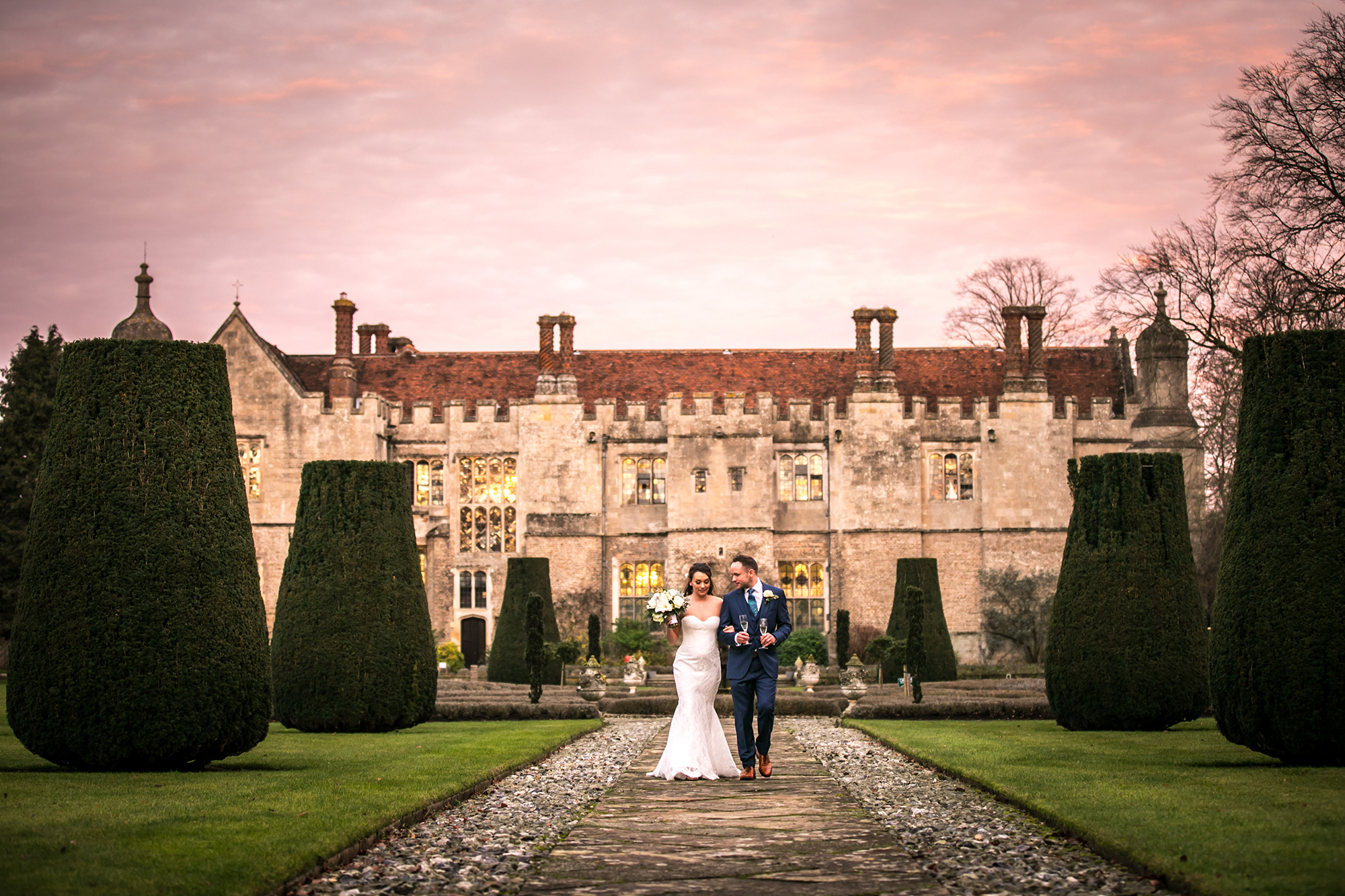 Newly married couple walking in front of Hengrave hall, with champagne through the gardens
